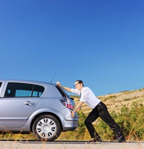 Young businessman pushing his car with empty fuel tank, shot with a tilt and shift lens